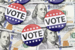 VOTE campaign buttons on top of hundred dollar bills